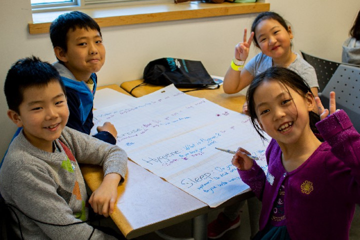 4 smiling kids at a workshop.